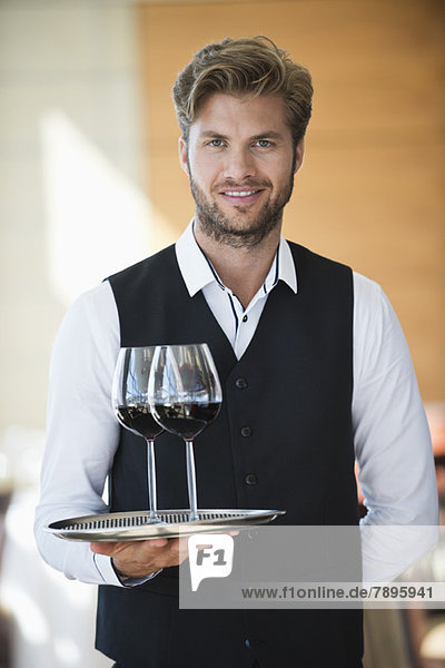 Portrait of a waiter holding a tray of wine glasses in a restaurant