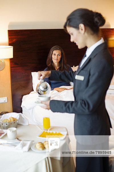 Kellnerin,  die einer Frau im Hotelzimmer Tee serviert.
