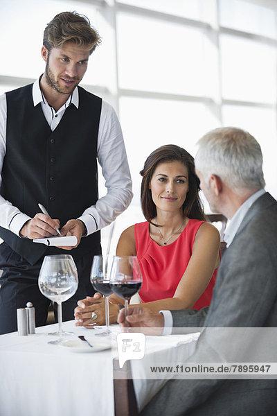 Kellner  der Bestellungen von einem Paar in einem Restaurant entgegennimmt.
