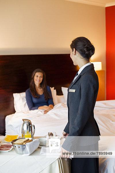 Kellnerin  die einer Frau im Hotelzimmer Essen serviert. Kellnerin, die einer Frau im Hotelzimmer Essen serviert.