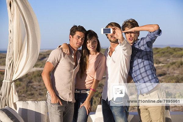 Gruppe von Freunden  die sich selbst mit dem Handy fotografieren