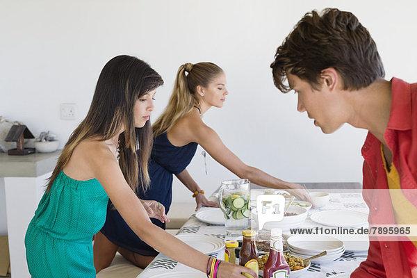 Freunde decken einen Esstisch