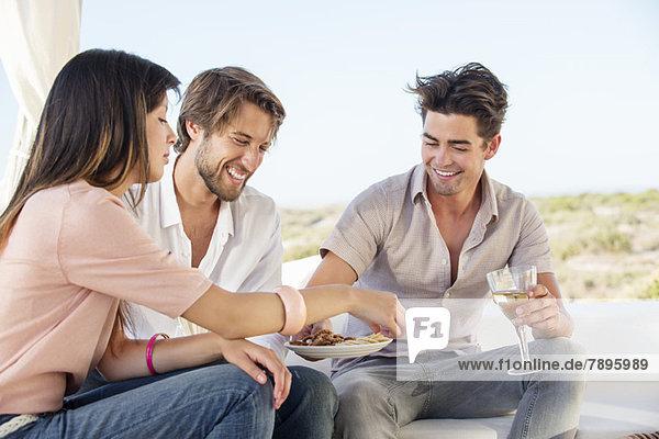 Drei Freunde genießen Snacks und Getränke im Freien