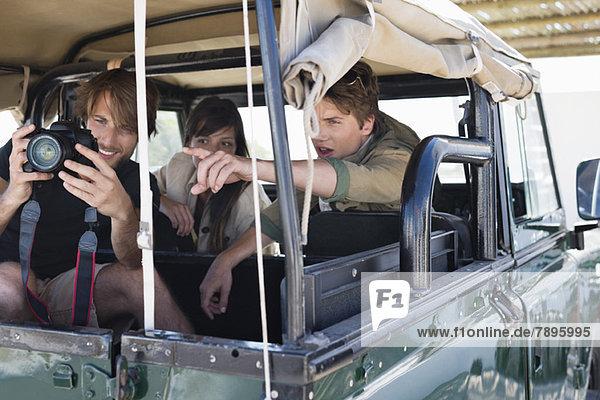 Mann fotografiert mit seinen Freunden in einem SUV