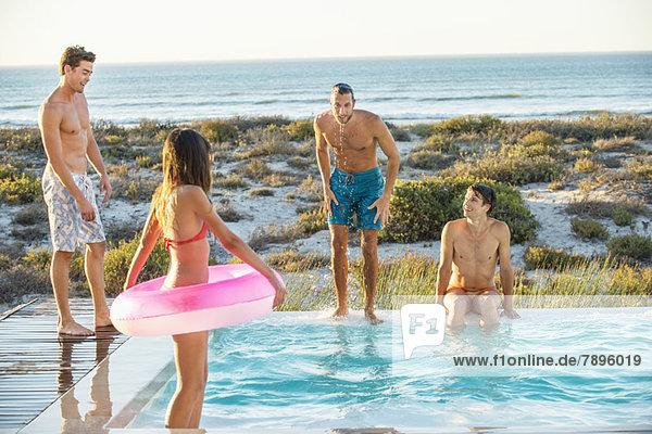Gruppe von Freunden  die sich in einem Schwimmbad am Strand vergnügen.