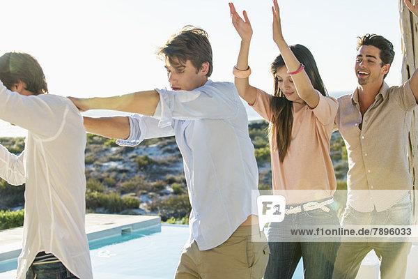 Gruppe von Freunden beim Tanzen am Pool