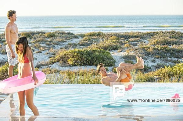 Drei Freunde  die sich an einem Swimmingpool am Strand vergnügen.