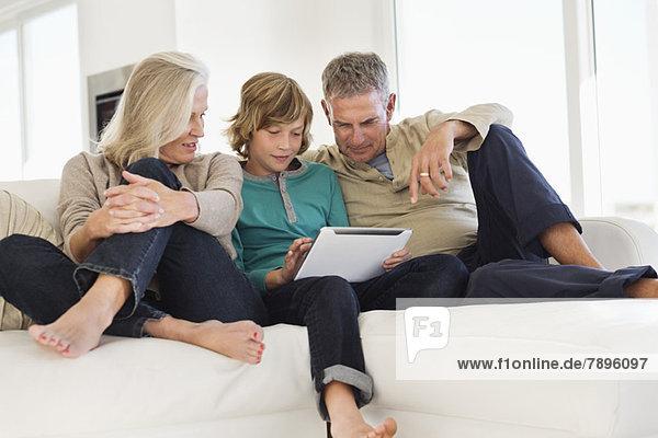Junge  der ein digitales Tablett mit seinen Großeltern auf einer Couch benutzt.