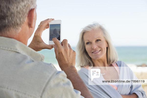 Mann fotografiert seine Frau mit einem Handy am Strand