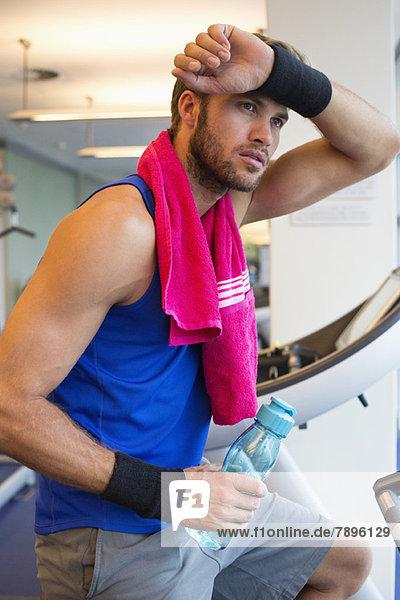 Mann mit einer Wasserflasche im Fitnessstudio