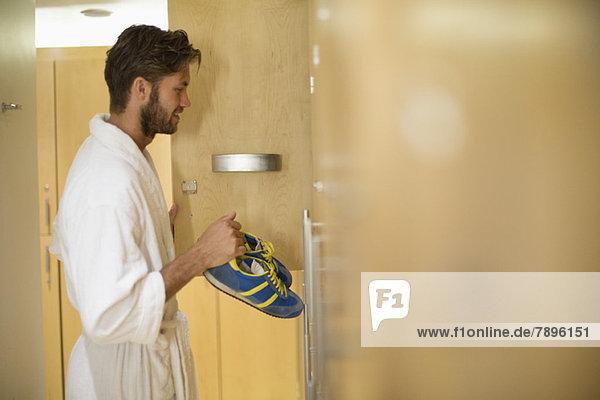 Ein Mann  der seine Schuhe in einen Umkleideraum im Spa stellt.