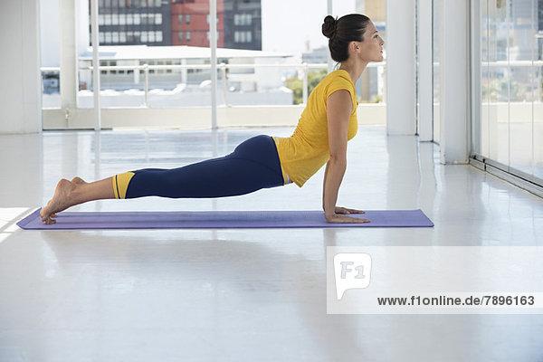 Frau trainiert auf einer Trainingsmatte im Fitnessstudio
