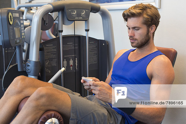 Mann  der auf einem Trainingsgerät sitzt und ein Mobiltelefon in einem Fitnessstudio benutzt.