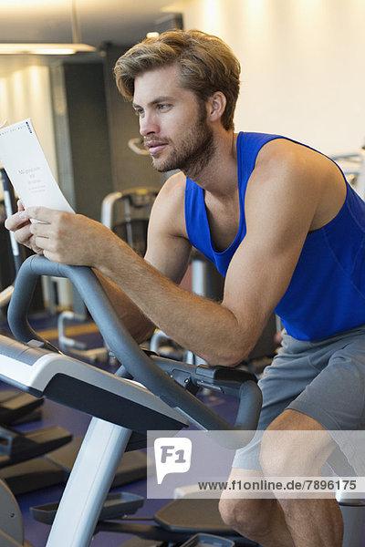 Mann beim Training an einer Maschine im Fitnessstudio