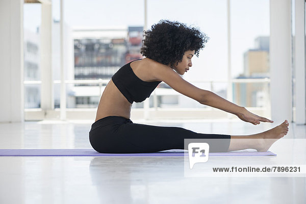Frau praktiziert Yoga auf einer Übungsmatte