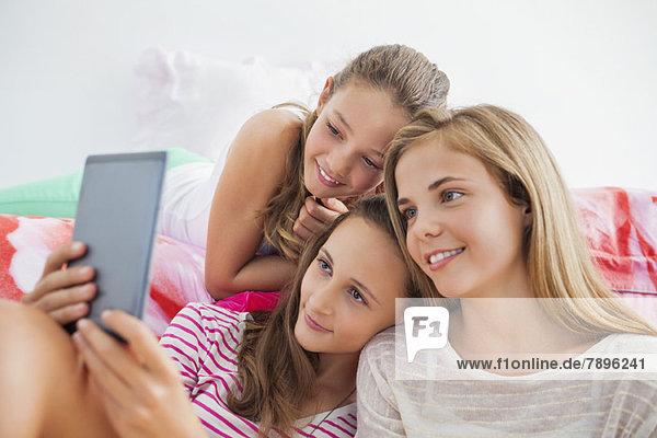 Drei Mädchen mit einem digitalen Tablett auf einer Pyjamaparty