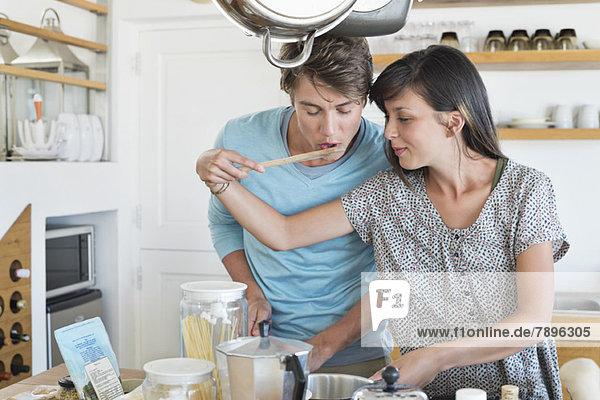 Frau  die ihrem Mann in der Küche das Essen schmeckt.