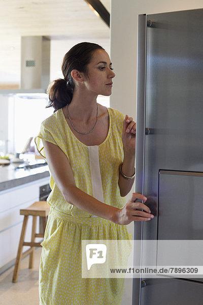 Frau öffnet einen Kühlschrank in der Küche