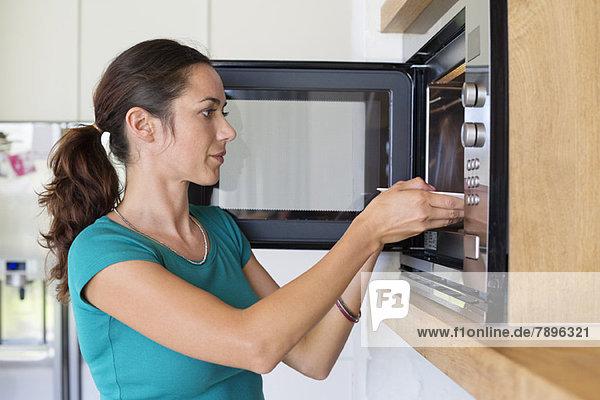 Frau stellt Essen in den Ofen