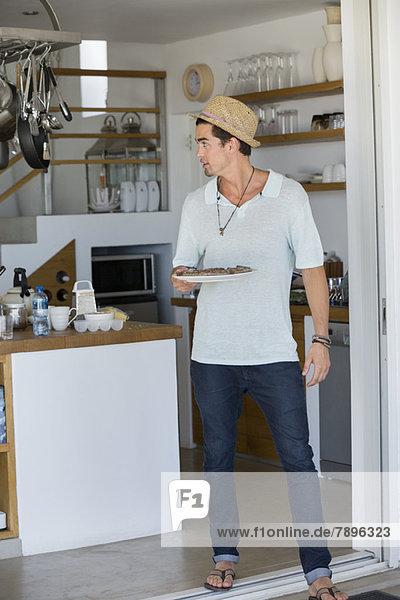Ein Mann hält einen Teller mit Essen in der Küche.