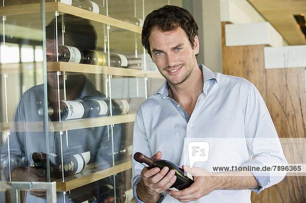 Porträt eines lächelnden Mannes mit einer Weinflasche