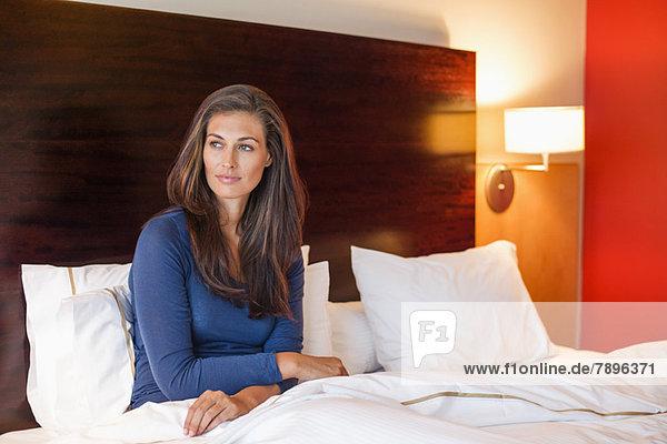 Frau im Hotelzimmer auf dem Bett sitzend Frau im Hotelzimmer auf dem Bett sitzend