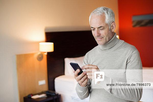 Ein Mann,  der ein Handy in einem Hotelzimmer benutzt.
