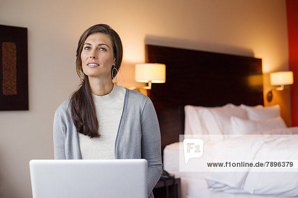 Woman using a laptop in a hotel room