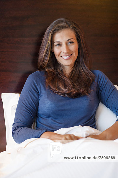 Woman smiling on the bed in a hotel room
