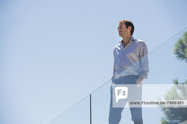 Mann  der auf der Terrasse steht und die Hände in den Taschen hat.