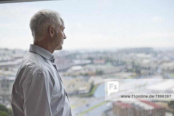 Mann schaut durch ein Fenster