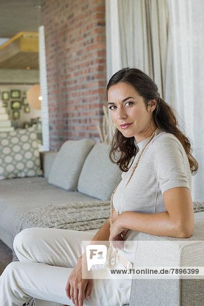 Porträt einer schönen Frau auf einer Couch sitzend