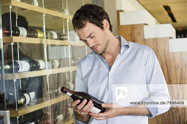Mann beim Betrachten einer Weinflasche
