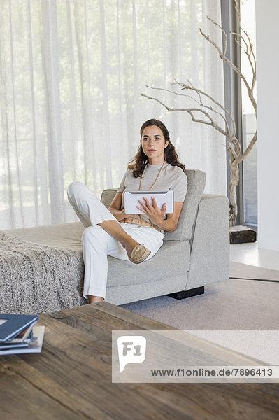 Schöne Frau  die ein digitales Tablett auf einer Couch benutzt.
