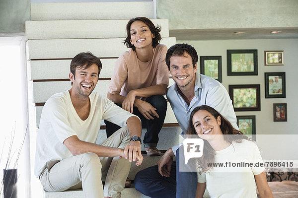 Porträt von lächelnden Freunden  die auf einer Treppe sitzen