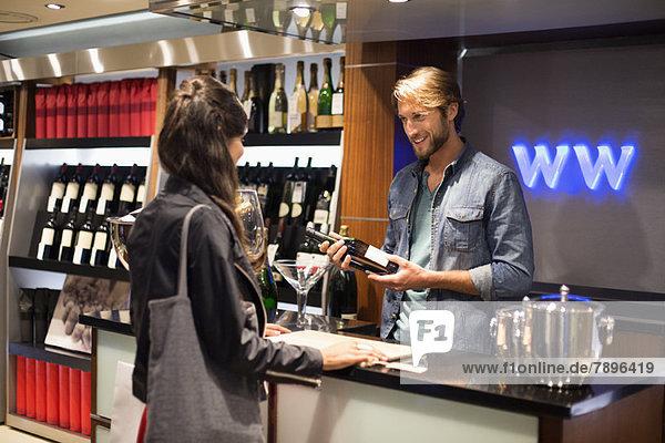 Verkäuferin  die einem Kunden eine Weinflasche schenkt.