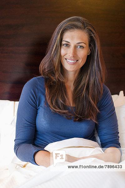 Frau lächelt auf dem Bett in einem Hotelzimmer