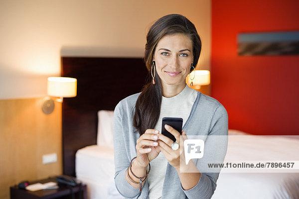 Frau mit Handy im Hotelzimmer