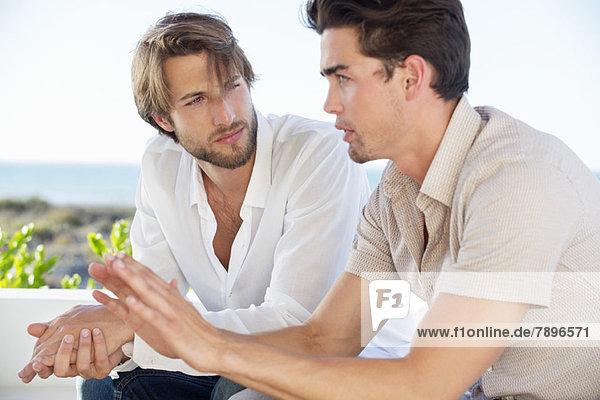 Zwei männliche Freunde sitzen zusammen und reden.
