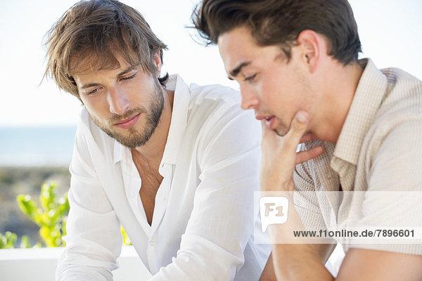 Zwei männliche Freunde sitzen zusammen
