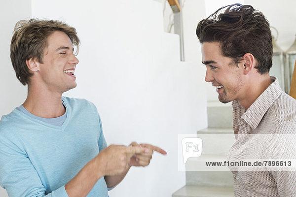 Zwei männliche Freunde  die miteinander reden.