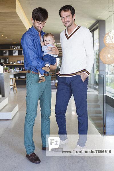 Eltern lächeln mit ihrem Sohn zu Hause