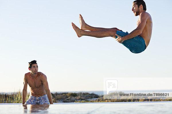 Ein Mann springt in ein Schwimmbad  sein Freund steht am Pool.