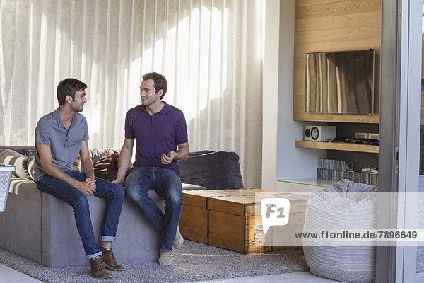 Zwei männliche Freunde sehen sich an und lächeln.