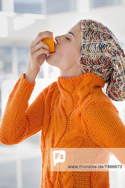 Frau drückt Saft aus einer Orange in den Mund