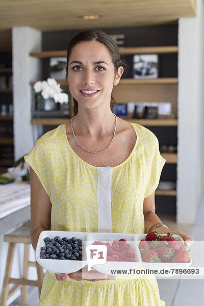 Porträt einer Frau  die zu Hause ein Tablett mit verschiedenen Beeren hält.