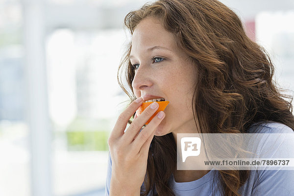 Close-up of a woman eating orange