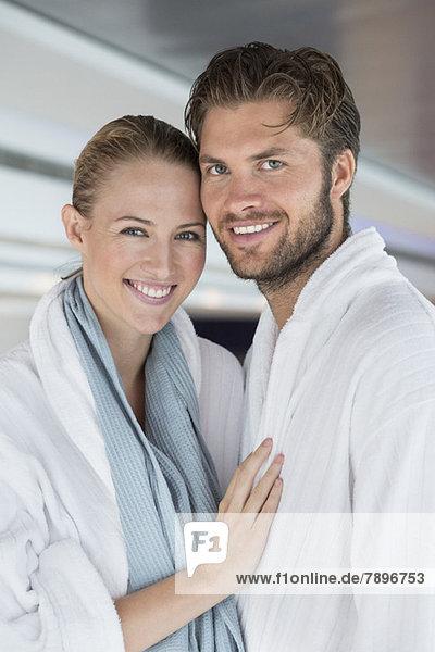 Porträt eines lächelnden Paares im Bademantel im Spa