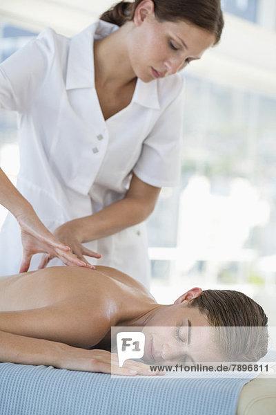 Frau erhält Rückenmassage von einem Massagetherapeuten