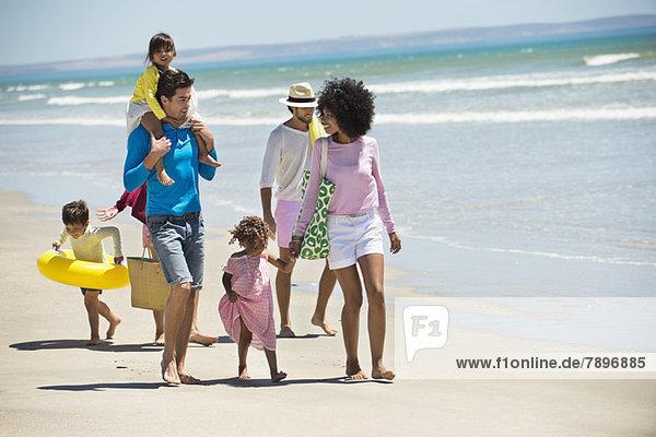 Familien  die am Strand spazieren gehen